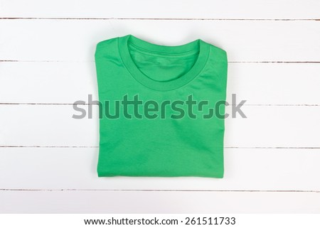 Green folded t-shirt on white wooden background - stock photo