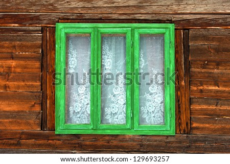Green frame window of the old rustic house on the background of wooden walls - stock photo
