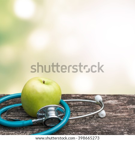 Green fresh organic natural nutrient apple with doctor's stethoscope heart shape on grunge old aged wood background blur bokeh:  World health day WHD symbolic conceptual design idea for healthy food - stock photo