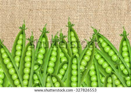 Green fresh peas over burlap background - stock photo