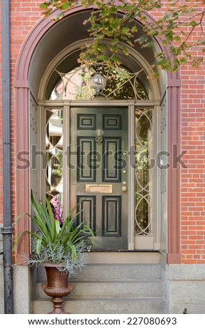 Green Front Door Under Brick Arch Entryway with Ivy and Potted Plant - stock photo