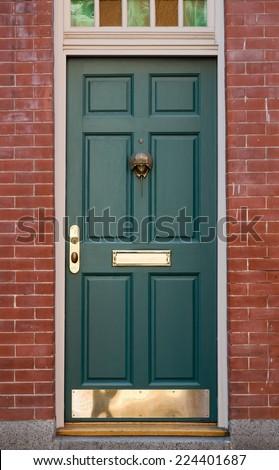 Green Front Door with Colorful Window Overhead in Brick Building - stock photo