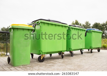 Green garbage containers in a row on stony street - stock photo