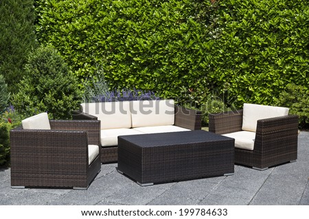 Green garden with an outdoor furniture lounge group with chairs, sofa and table in a patio - stock photo