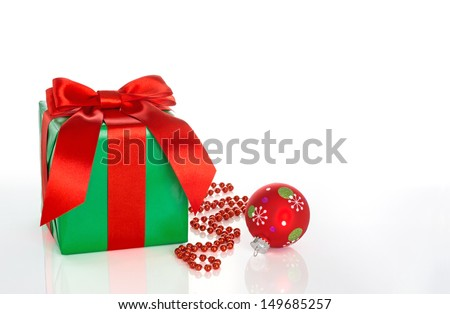 Green gift box with red bow, red beads, red Christmas ornament on white, with reflection and copy space - stock photo