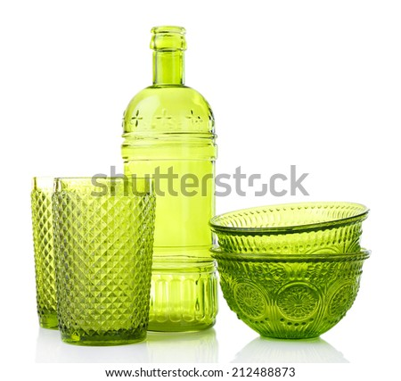 Green glass bottle, bowls and glasses, isolated on white - stock photo
