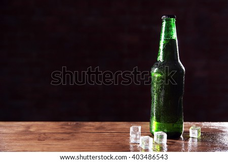 Green glass bottle of beer and ice cubes on dark background, close up - stock photo