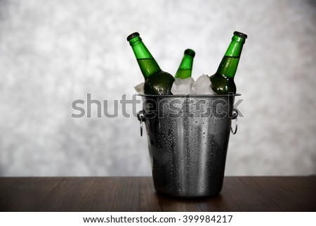 Green glass bottles of beer in ice-pail on grey background - stock photo