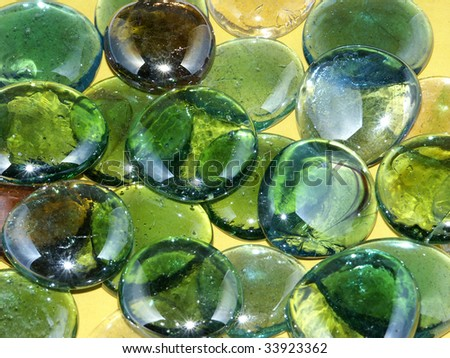 Green glass marbles on yellow background - stock photo