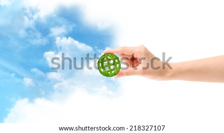 Green globe in hand isolated on white and sky background - stock photo