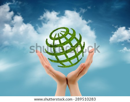 Green globe in hands on sky with cloud background. Environmental concept - stock photo