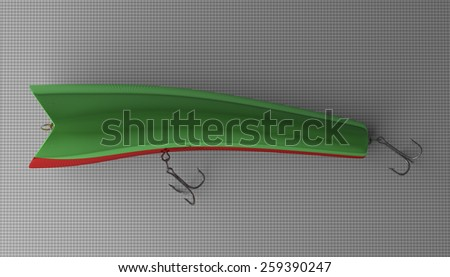Green glossy fishing plug with red belly and two treble hooks lying on gray checkered background - stock photo