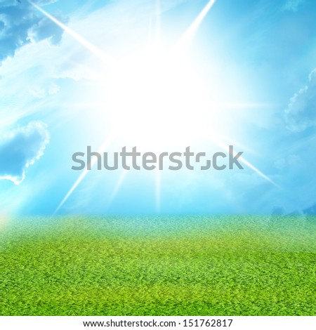 green grass and blue sky with clouds and intense sunlight - stock photo