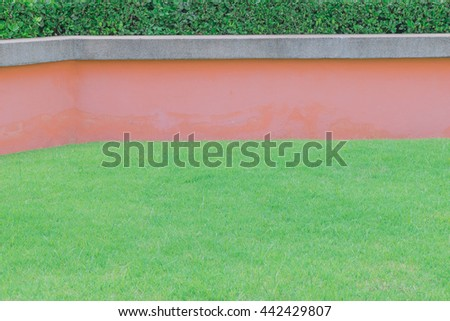 Green grass and concrete pink wall background. Geometric stripes pattern exterior natural green grass and concrete sandstone wall with tree fence decorative background in garden - stock photo
