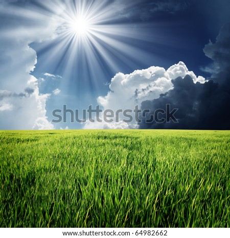 Green grass and storm sky with clouds - stock photo
