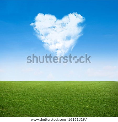 green grass field and blue sky with clouds in shape of heart - love concept - stock photo