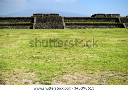 Green grass field and Teotihuacan ruins - stock photo
