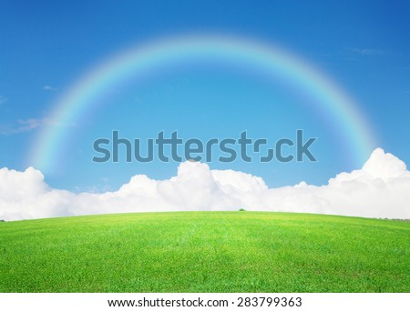 Green grass field, blue sky with clouds on horizon and rainbow background - stock photo