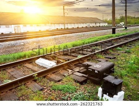 Green grass near rails along industrial station - stock photo