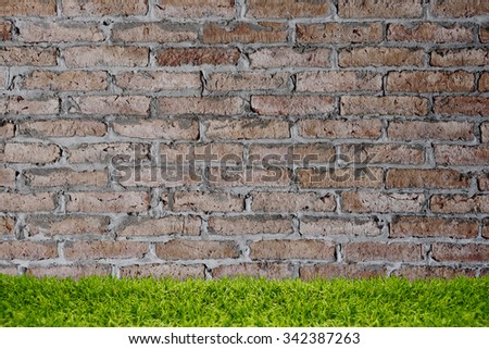 Green grass over brick wall background. - stock photo