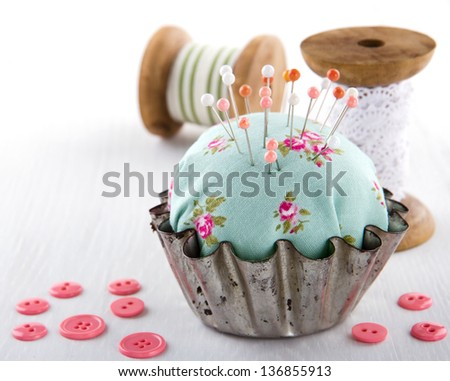 Green handmade floral pincushion in an old metal cupcake with buttons and spools of thread and lace, sewing concept background - stock photo