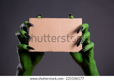 Green hands with black nails holding empty piece of cardboard, Halloween theme   - stock photo