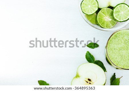 Green healthy drink. Vegetable juice, apple, sliced lime, on the white wooden background. Vegetarian food. Detox - stock photo