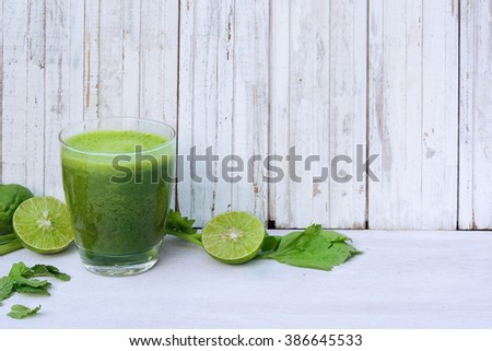 Green healthy drink. Vegetable juice, sliced lime, leaves of mint and celery on the white wooden background. Vegetarian food. Detox - stock photo