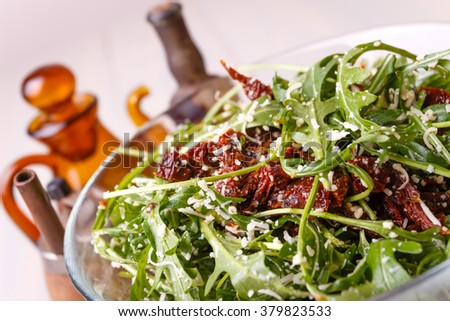 Green healthy salad with arugula and sun-dried tomatoes and parmesan cheese on a wooden kitchen table. Pepper, peppermoll, utensils for olive oil, vinegar and seasonings. Italian cuisine - stock photo