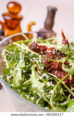 Green healthy salad with arugula and sun-dried tomatoes and parmesan cheese on a wooden kitchen table. Pepper, peppermoll, utensils for olive oil, vinegar and seasonings. Italian cuisine.  - stock photo