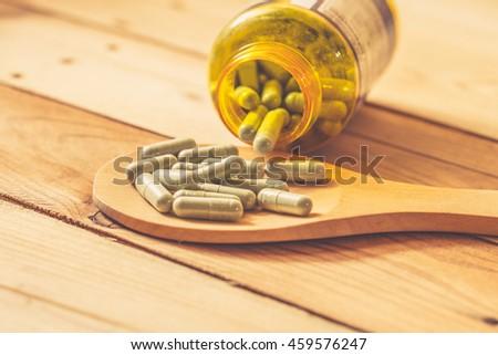 green herbal powder in capsule on wood background, Dried Kariyat for medicine. - stock photo