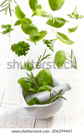green herbs falling into mortar and pestle on white wooden table - stock photo