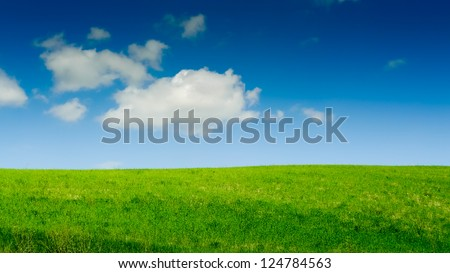 Green hill under a blue sky filled with clouds on a sunny day in Tuscany, Italy - stock photo