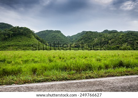 Green hills and field  with moody sky  - stock photo