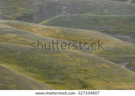 Green hills in the barren mountains of the Monti Sibillini in Umbria, Italy - stock photo