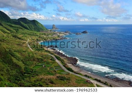 Green hills overlook the white waves crashing on the shoreline. - stock photo