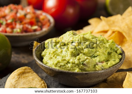 Green Homemade Guacamole with Tortilla Chips and Salsa - stock photo