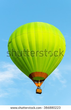 Green hot air balloon in flight against the blue sky. - stock photo