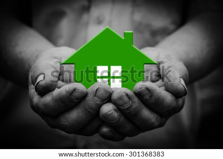 Green house is in the holding hands with dark corners. - stock photo