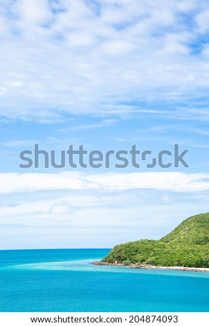 Green island and blue sea in summer - stock photo