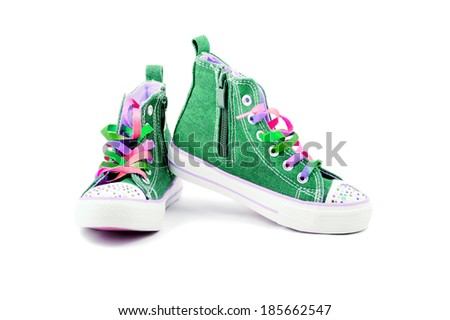 Green jeans sneakers with rainbow laces isolated on white - stock photo