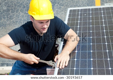Green job series - young electrician repairs solar panel. - stock photo