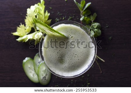 Green juice with apple, cucumber, mint,lettuce, dill and parsley on wooden table. - stock photo