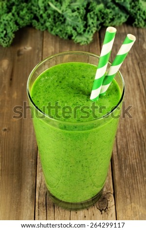 Green kale smoothie in a glass with straws on a rustic wood background - stock photo