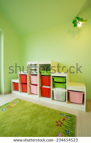 Green kid's room with modern plastic furniture - stock photo