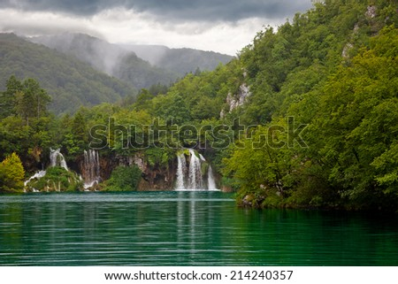 Green lake at Plitvice Lakes National Park in Croatia with waterfall. - stock photo