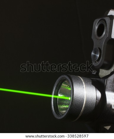 Green laser on at the bottom of a handgun - stock photo