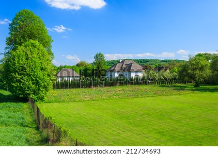 Green lawn and houses in countryside landscape of Poland near Krakow town on sunny summer day - stock photo