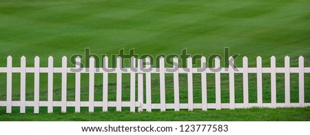Green lawn and white wood fence - stock photo