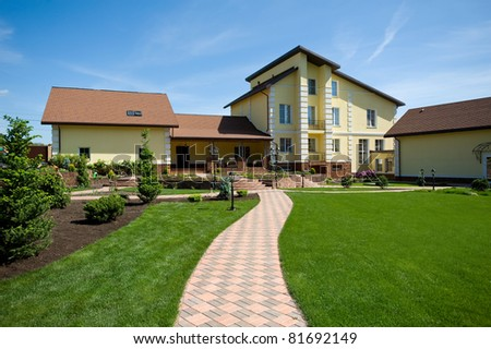 green lawn opposite country cottage - stock photo